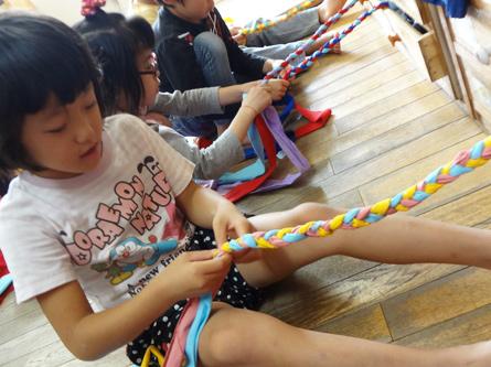 """5歳児『三つあみの取り組み』<br>年長では三つあみで作った縄とびを作成しています。それを年中クラスの子どもたちへ、""""楽しくあそんでほしい""""と願いを込めてプレゼントしています。4歳児の子は、世界でたった一つの自分の縄とびに大喜び!すぐに跳ぶ練習を始めています。"""