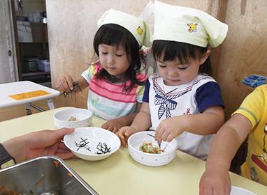 1歳児『パラパラクッキング』<br> 自分たちでのりをパラパラかけて給食のキャベツの和え物をつくりおいしく食べました。