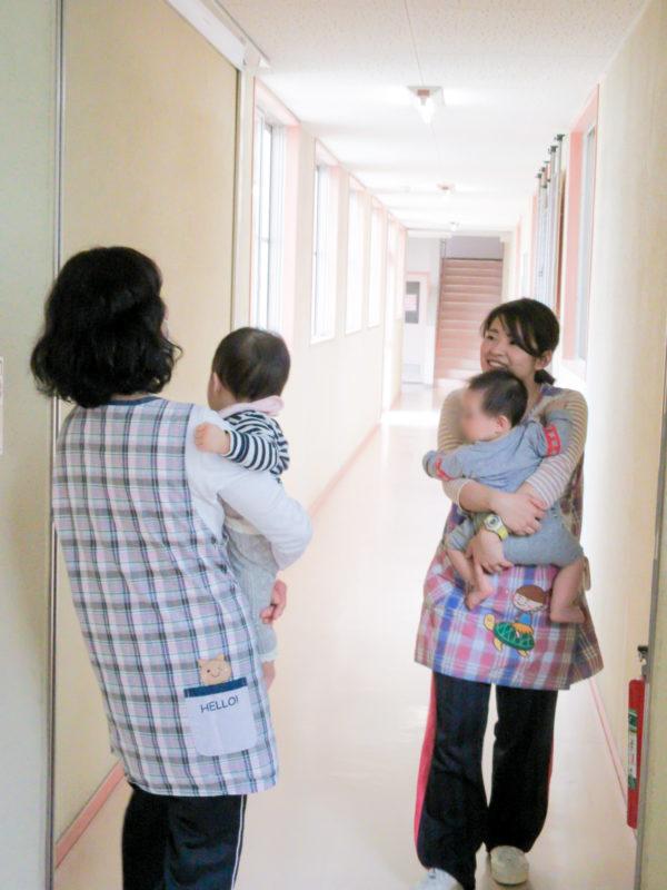 写真:廊下で挨拶する保育士と子ども